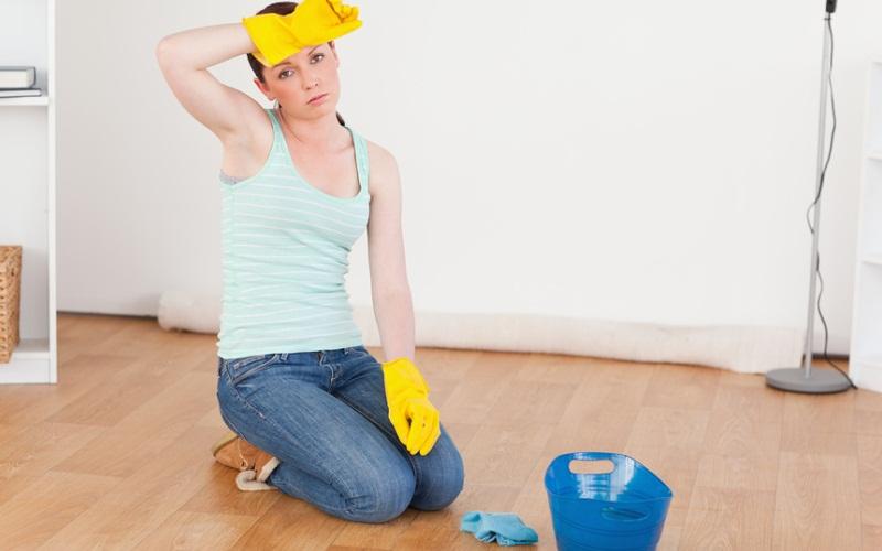 Симпатичная молодая женщина утирает пот со лба, отмывая пол в комнате