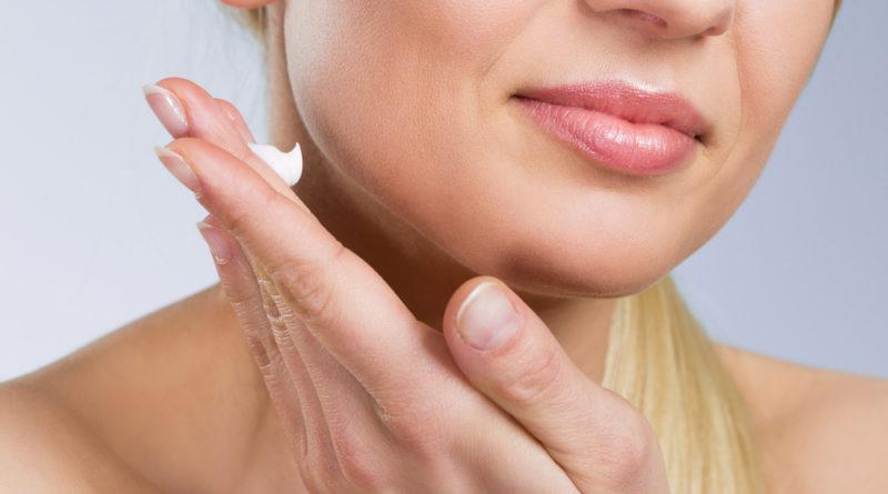 woman-applying-cream-on-face